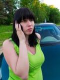 A menina fala pelo telefone sobre o carro Foto de Stock