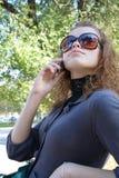 A menina fala por um telefone móvel Imagens de Stock