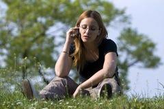 A menina fala por um telefone móvel no parque. foto de stock royalty free