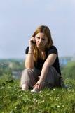 A menina fala por um telefone móvel no parque. Imagem de Stock