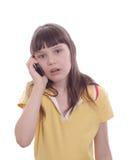 A menina fala por um telefone móvel. Surpresa Imagens de Stock
