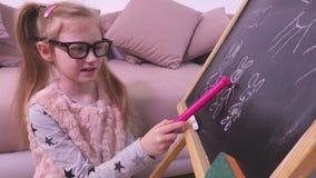 A menina fala sobre o desenho em um quadro-negro video estoque