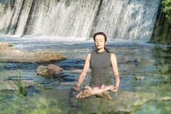 A menina faz a ioga no fundo de uma cachoeira fotografia de stock