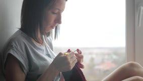 A menina faz malha um lenço na janela filme