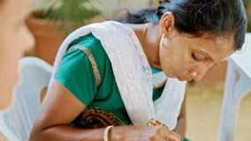 A menina faz a pintura tradicional com hena nos dedos da noiva ilustração stock