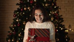 A menina faz um desejo e abre um pacote do presente do Natal o conceito dos feriados e do ano novo a menina está feliz e filme