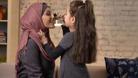 A menina faz a uma compensação sua mãe muçulmana no hijab, escova da composição, rindo, família de sorriso, idílio, conforto home filme