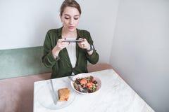 A menina faz uma foto do alimento no telefone Mulher que senta-se em um restaurante e que fotografa o alimento no tempo do almoço imagens de stock