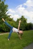 A menina faz uma roda em uma grama. fotos de stock royalty free