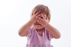 A menina fechou seus olhos com suas mãos Fotografia de Stock Royalty Free