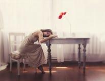A menina feericamente bonita que senta-se na tabela com o seu eyes fechado, com flores Fotografia de Stock