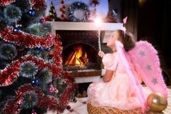 Menina feericamente pequena perto de uma árvore de Natal fotografia de stock royalty free