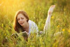 A menina feliz é de encontro e de leitura um livro foto de stock royalty free