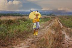 A menina feliz é em posses do campo um guarda-chuva amarelo Imagem de Stock Royalty Free