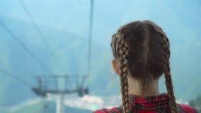 Menina feliz adorável na cabine no teleférico nas montanhas no fundo da paisagem beautful filme