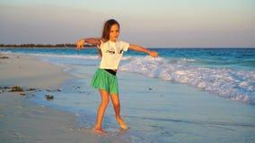 Menina feliz adorável na praia branca no por do sol Dança bonito da criança no litoral tropical no vídeo de movimento lento vídeos de arquivo