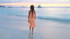 Menina feliz adorável que anda na praia branca no por do sol vídeo de movimento lento video estoque