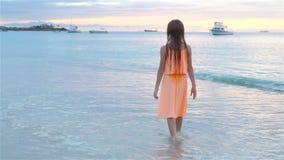 Menina feliz adorável que anda na praia branca no por do sol vídeo de movimento lento vídeos de arquivo