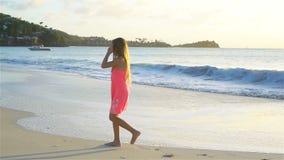 Menina feliz adorável que tem o divertimento na praia branca no por do sol vídeo de movimento lento vídeos de arquivo