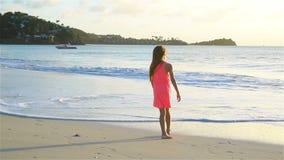 Menina feliz adorável que tem o divertimento na praia branca no por do sol vídeo de movimento lento video estoque