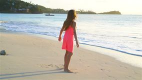 Menina feliz adorável que tem o divertimento na praia branca no por do sol vídeo de movimento lento filme