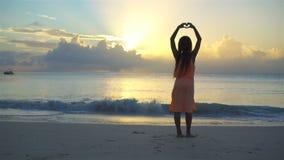 A menina feliz adorável tem muito divertimento na praia branca no por do sol vídeos de arquivo