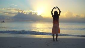A menina feliz adorável tem muito divertimento na praia branca no por do sol video estoque