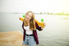 Menina feliz alegre do skater no equipamento do moderno que tem o divertimento em um cais de madeira durante férias de verão imagens de stock royalty free