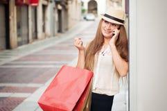 A menina feliz anda através da rua após a compra Ela que guarda fotos de stock royalty free