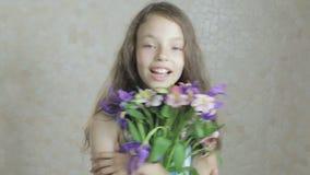 A menina feliz bonita aprecia flores do ramalhete das íris e do alstroemeria video estoque