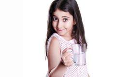 Menina feliz bonita com cabelo escuro longo e o vestido que guardam o vidro da água foto de stock royalty free