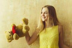 Menina feliz bonita com o brinquedo do urso de peluche no vestido amarelo imagem de stock royalty free
