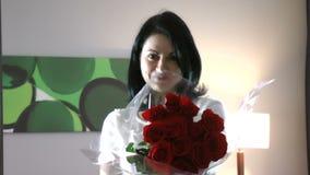 A menina feliz bonita dá a uma rosa vermelha flores video estoque