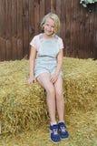 A menina feliz bonita do preteen vestiu-se nos macacões curtos do babador que sentam-se em um feno na vila Estilo country Imagens de Stock Royalty Free