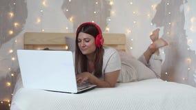A menina feliz bonita encontra-se em uma cama grande usando um computador móvel da cor branca e escuta-se a música nos fones de o video estoque