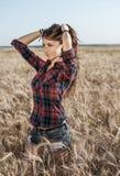 Menina feliz bonita no campo, tarde ensolarada, camisa do short O conceito de apreciar a natureza Resto no ar Imagens de Stock Royalty Free