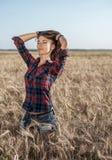 Menina feliz bonita no campo, tarde ensolarada, camisa do short O conceito de apreciar a natureza Resto no ar Foto de Stock