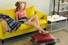 menina feliz bonita no chapéu que guarda o bilhete do passaporte e de ar ao sentar-se no sofá fotografia de stock royalty free