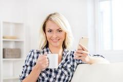 Menina feliz bonita no sofá com um copo do chá imagem de stock royalty free