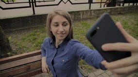 Menina feliz bonita que faz o selfie no parque em um banco vídeos de arquivo