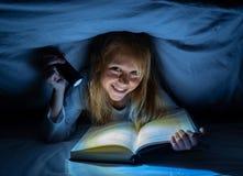 Menina feliz bonita que lê um livro na escuridão que esconde sob a edredão na cama com luz instantânea foto de stock