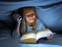Menina feliz bonita que lê um livro na escuridão que esconde sob a edredão na cama com luz instantânea imagens de stock