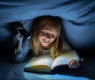 Menina feliz bonita que lê um livro na escuridão que esconde sob a edredão na cama com luz instantânea imagens de stock royalty free