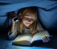Menina feliz bonita que lê um livro na escuridão que esconde sob a edredão na cama com luz instantânea foto de stock royalty free