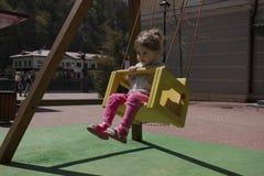 Menina feliz bonito, criança que tem o divertimento em balanços no campo de jogos Dia de mola ensolarado Imagens de Stock Royalty Free