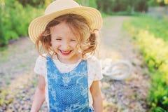 Menina feliz bonito da criança com a bicicleta na estrada ensolarada do verão Imagens de Stock Royalty Free