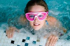 Menina feliz bonito na máscara cor-de-rosa dos óculos de proteção na piscina Foto de Stock
