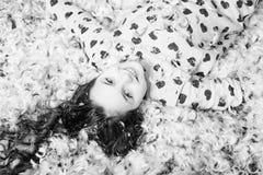 Menina feliz bonito no assoalho coberto com para baixo e na pena fotografia de stock