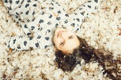 Menina feliz bonito no assoalho coberto com para baixo e na pena fotografia de stock royalty free