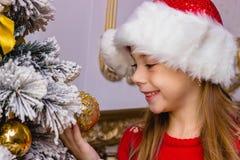 A menina feliz bonito no chapéu vermelho pendura decorações Fotografia de Stock